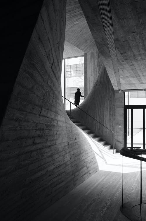 Person Standing Near Window Inside Building Near Stairs Grayscale Photo