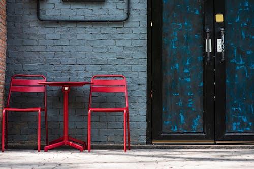 Red Metal Chair Beside Blue Wooden Door