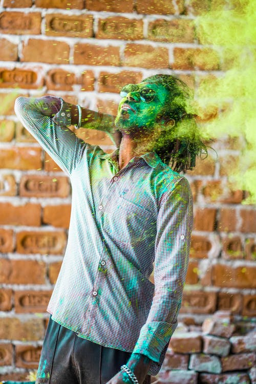 Man in White and Gray Plaid Button Up Shirt With Green Powder on His Face