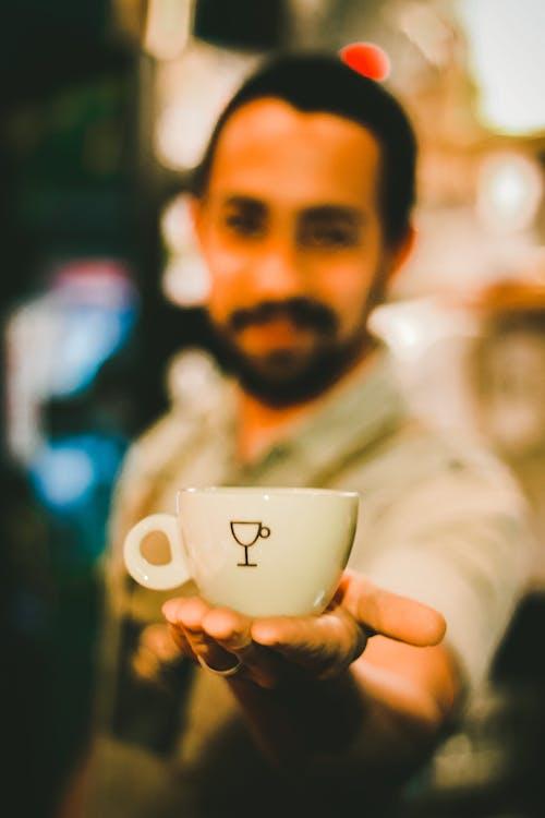 Focus Photography of Man Holding Ceramic Teacup