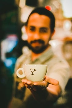 Focus Photography of Man Holding Ceramic Teacup