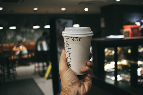 Person Holding Labeled Disposable Cup