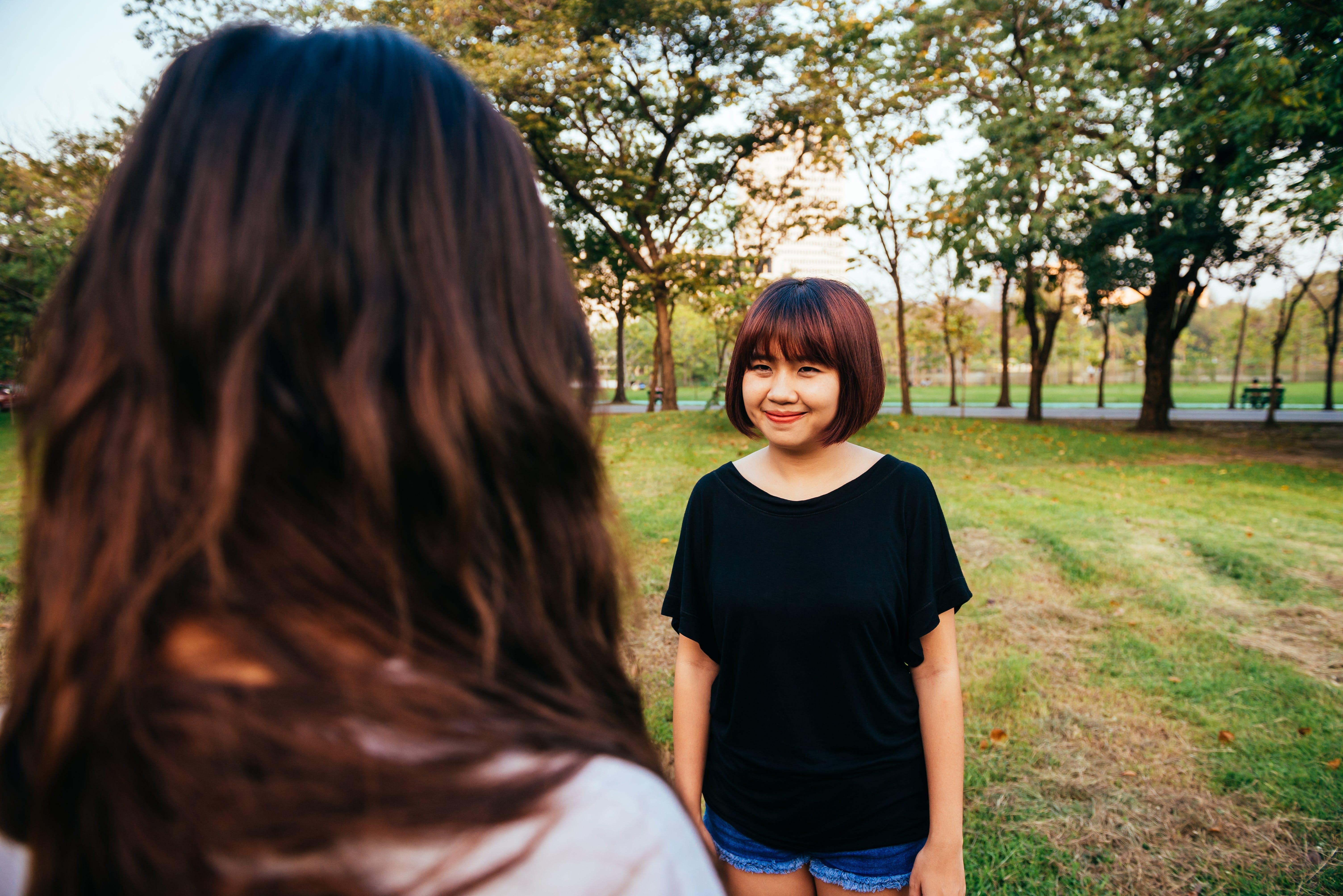 Woman Wearing Black Boat-neck Shirt on Green Grass