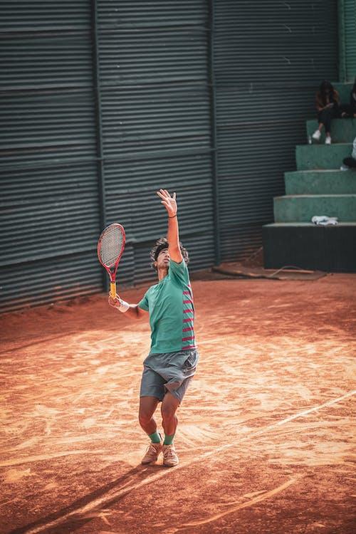 Man in Blue Shirt Playing Tennis