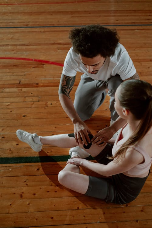 Overhead Shot of a Man Putting a Kinesio Tape on a Woman's Injured Knee