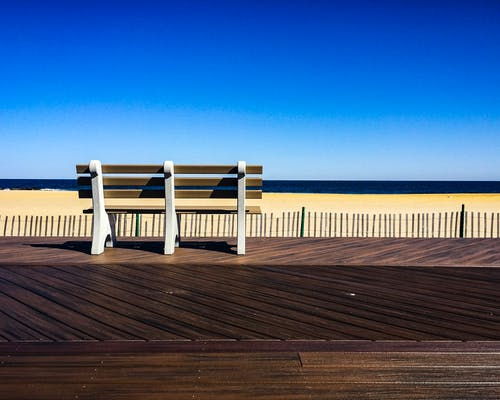 Brown-and-white Wooden Bench Facing Body of Water Under Clear Blue Sky