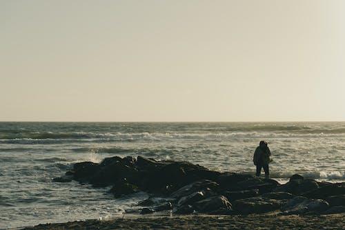 Unrecognizable person standing on rocky coast