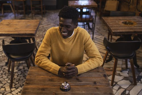 Man in Yellow Sweater Sitting at Wooden Table
