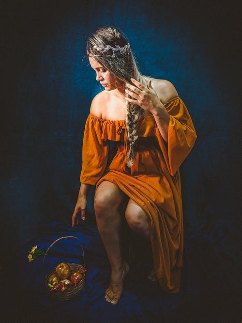 Woman in Orange Dress Sitting on Blue and Gold Ball