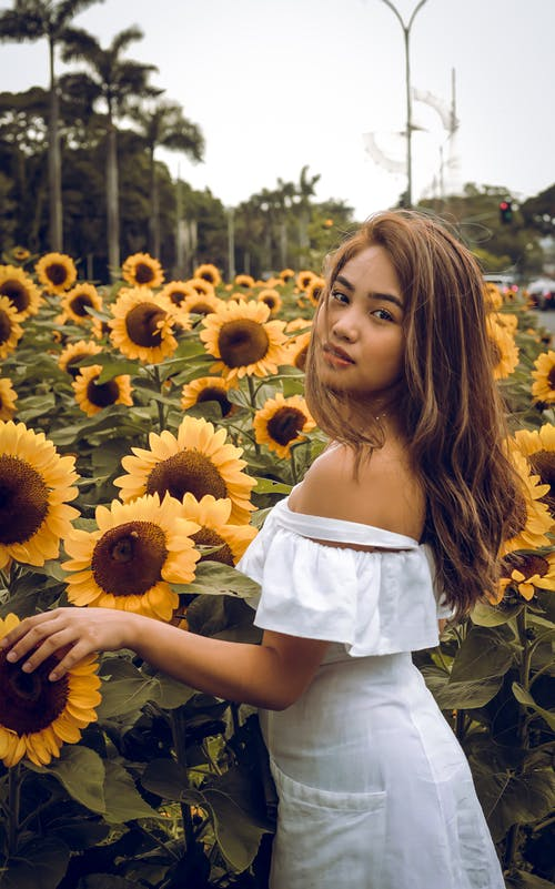 Woman in White Off Shoulder Dress Standing on Sunflower Field
