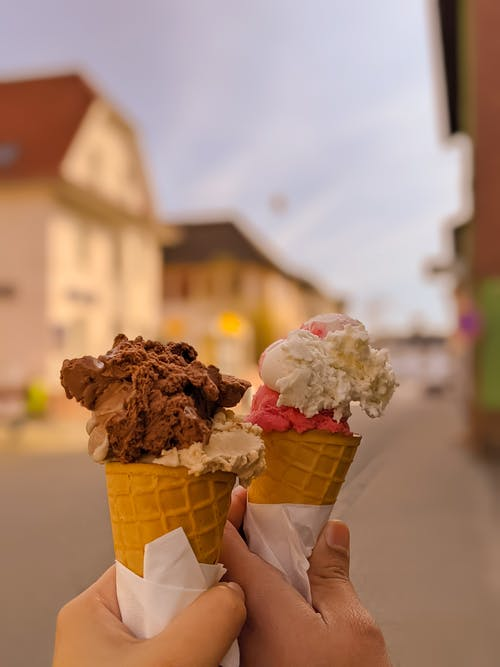 Crop persons with ice creams