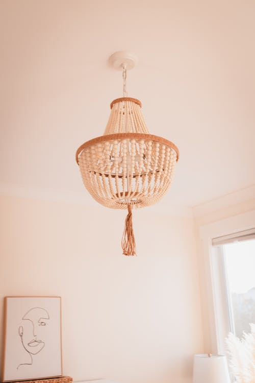 From below of elegant chandelier with decorative elements hanging on ceiling and picture on beige wall in light room