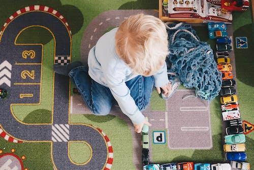 Kostenloses Stock Foto zu junge, der mit spielzeugautos spielt