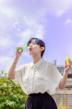 Photo of Woman in White Blouse Playing With Bubbles
