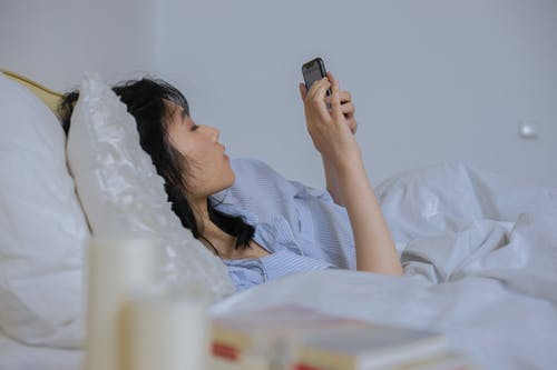 A Woman Using a Smartphone While Lying Down on a Bed