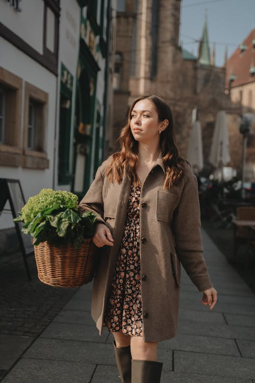 Woman in Brown Coat Holding Basket of Green Leaves