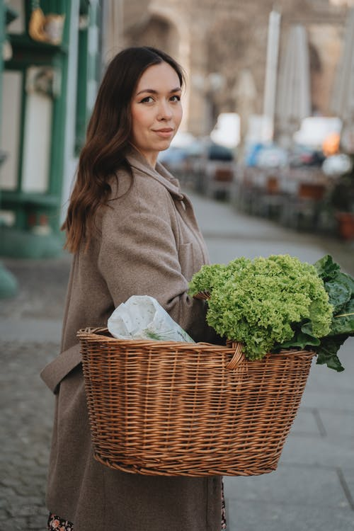 Woman in Brown Coat Carrying Wicker Basket with Fresh Green Vegetables