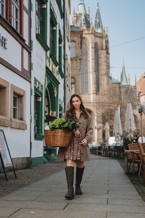 Woman Walking on Sidewalk Carrying Wicker Basket