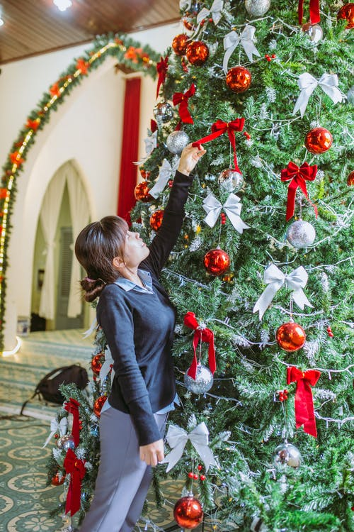 Woman Putting Ribbon Bow on Christmas Tree
