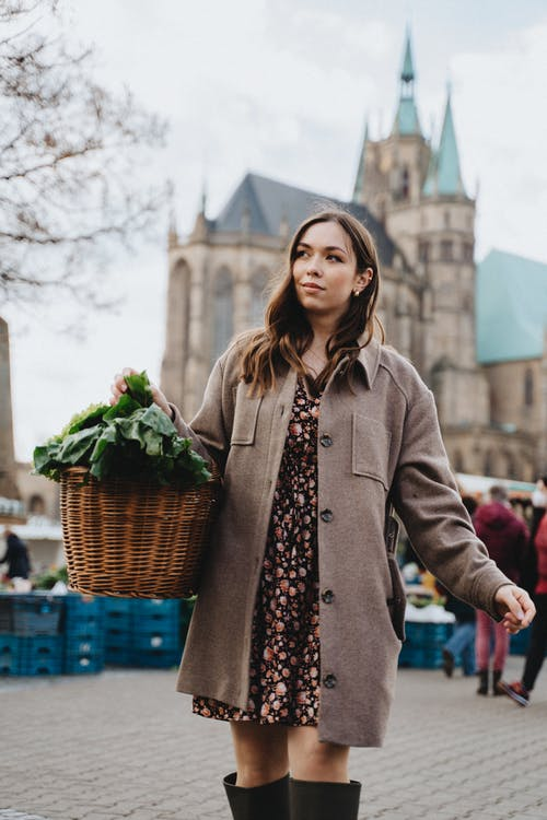 Womna Carrying a Wicker Basket Full of Green Vegetables