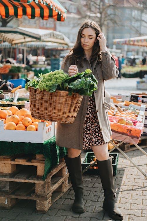 Woman in Brown Coat Carrying Wicker Basket Full of Green Vegetables