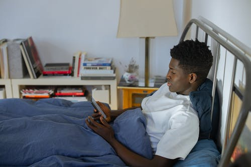 Man Using Phone while on Bed