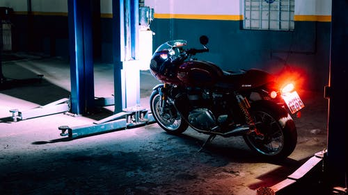 Black and Red Motorcycle Parked Beside Blue and White Wall