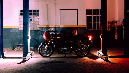 Black and Red Motorcycle Parked Beside White Wall