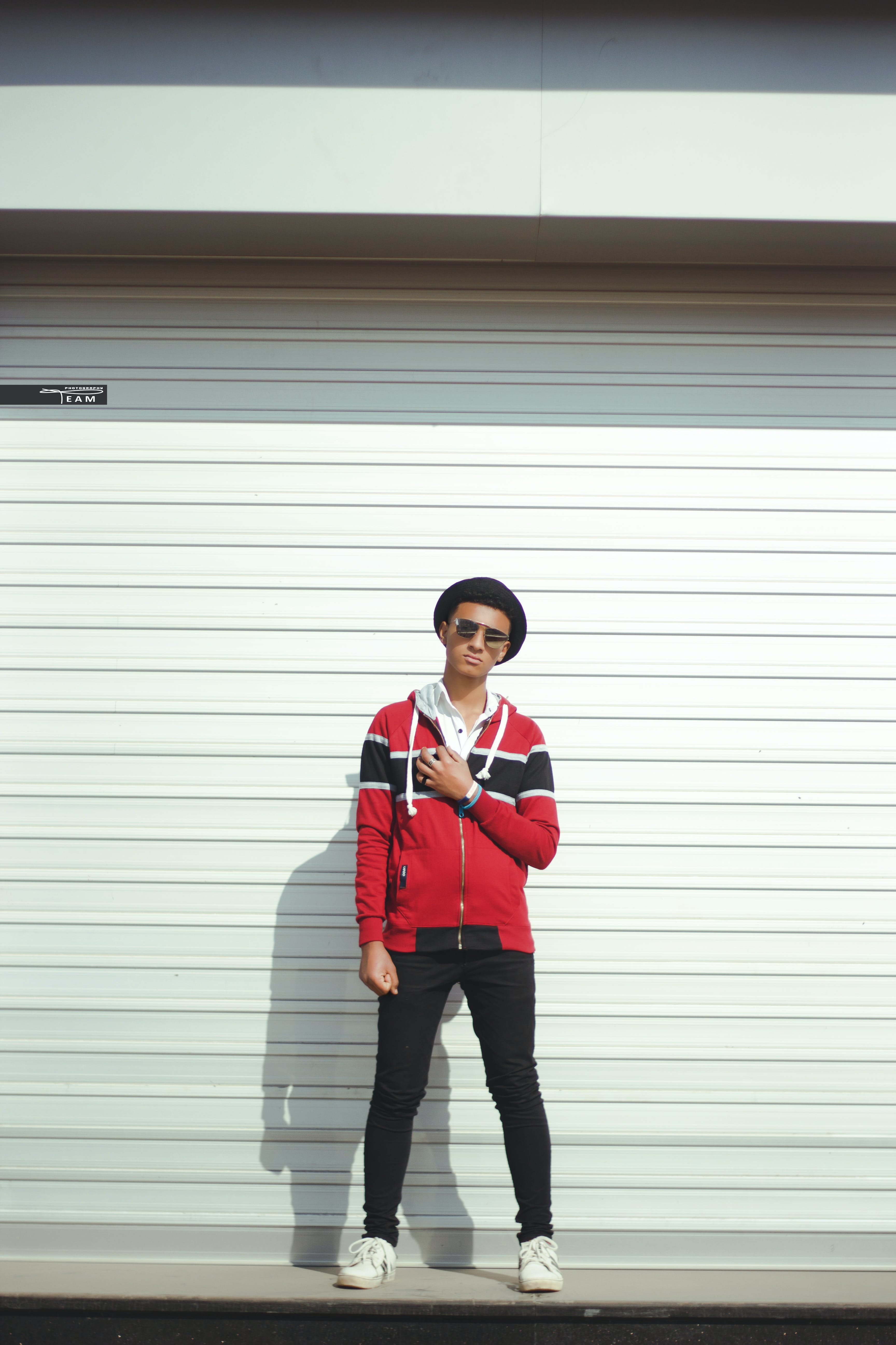 Man In Red And Black Zip-up Jacket And Black Pants With Black Hat
