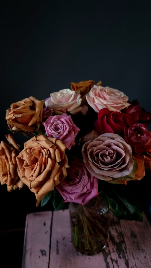 Blooming aromatic roses of different colors in glass vase placed on shabby wooden table in dark studio