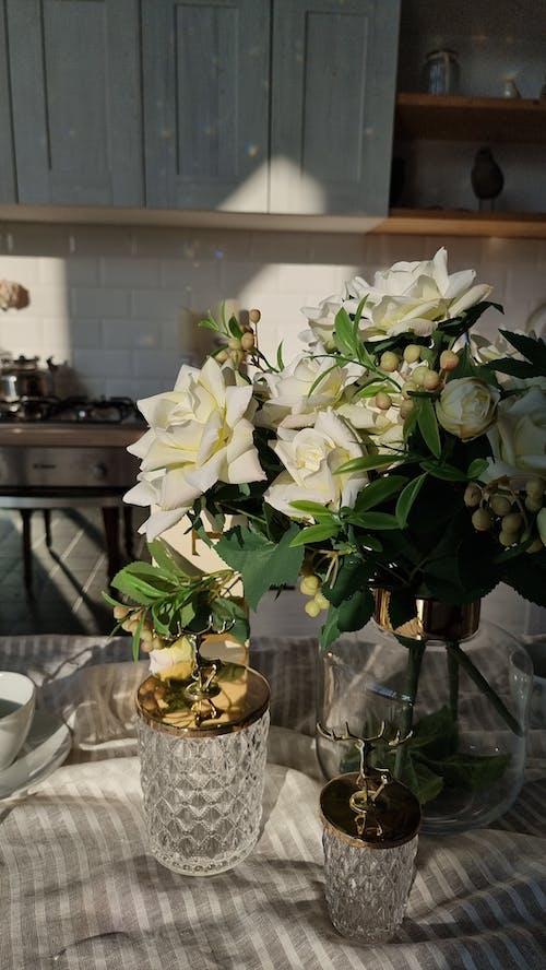 Delicate white roses in vase near elegant cut glass tableware in light modern dining room