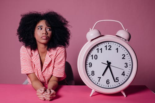 Woman in Pink Long Sleeve Shirt Sitting Beside White and Pink Alarm Clock