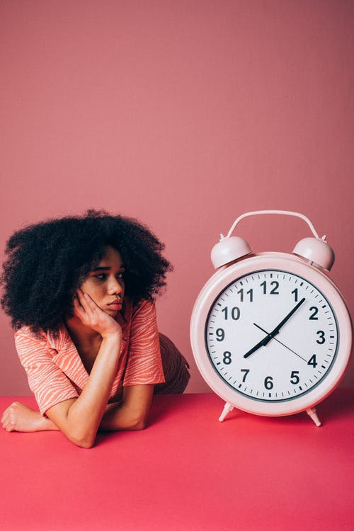 Woman Looking at a Big Pink Alarm Clock