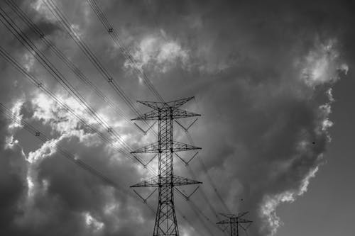 Electric towers under shiny cloudy sky in evening