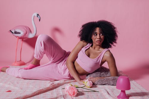 Woman in Pink Crop Top and Jogging Pants on Pink Background