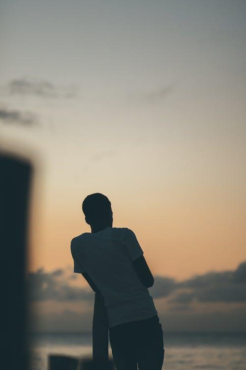 Man in Black Shirt Standing during Sunset