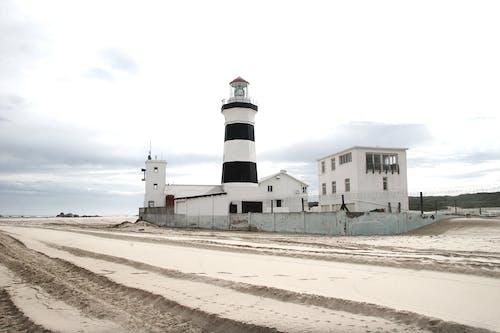 Striped lighthouse on sandy seashore