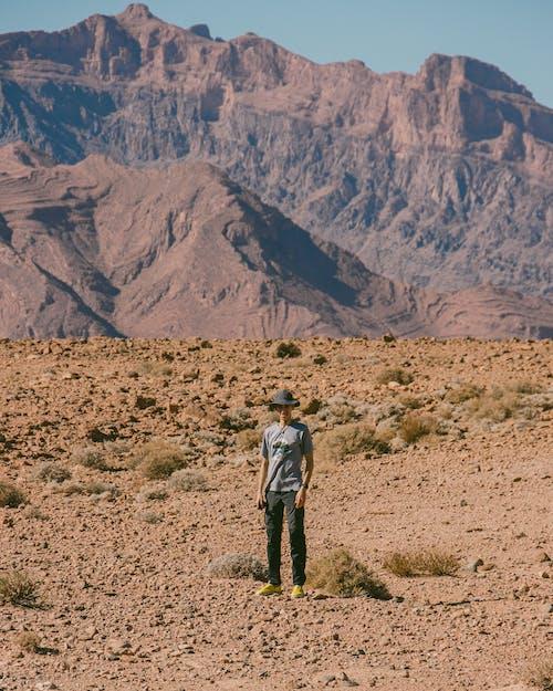 Man in Blue Jacket Walking on Brown Field