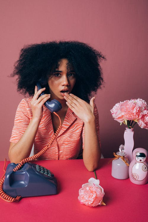 Woman Looking Surprised while Using an Old Telephone