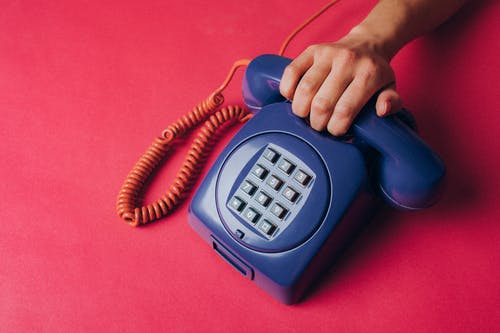 Person Holding an Old Corded Telephone