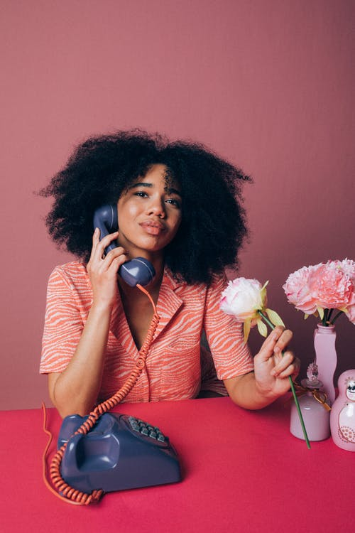 Woman Using an Old Telephone while Holding a Pink Rose