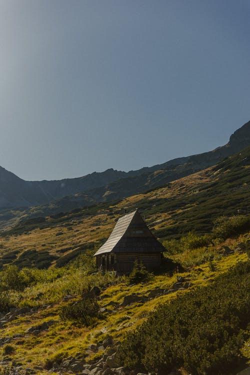 Brown Wooden House on Green Grass Field Near Mountain