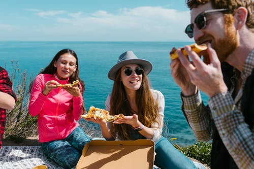 Woman in Yellow Cardigan Sitting Beside Woman in Blue Denim Jeans Holding Bread