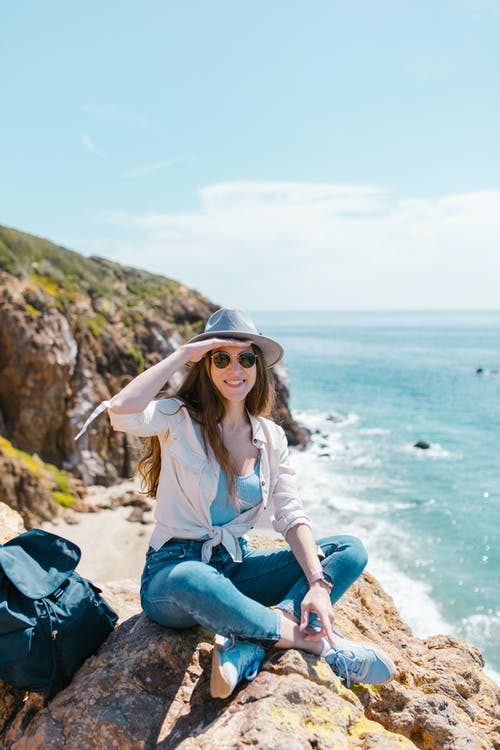 Woman in White Shirt and Blue Denim Jeans Sitting on Rock Formation Near Sea