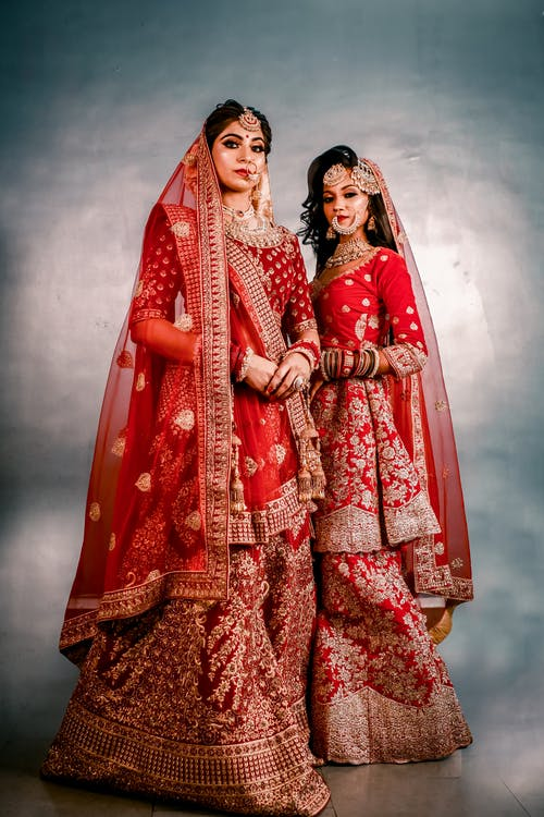 2 Women in Red and Brown Traditional Dress
