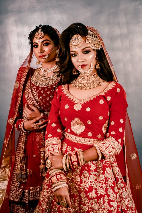 Woman in Red and White Floral Dress Beside Woman in Red and Gold Sari