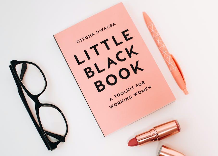 Little Black Book Surrounded With Pink Click Pen, Red Lipstick, and Black Wayfarer Eyeglasses