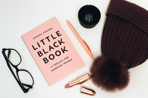 Little Black Book Beside Eyeglasses and Lipstick Case