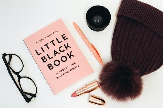 Little Black Book Beside Eyeglasses and Lipstick Case
