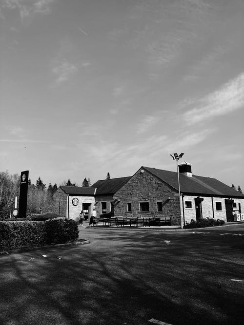 Black and white exterior of modern rural brick cottages located in village on clear spring day